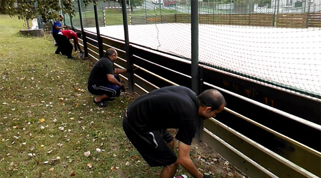 As part of community work, Romani residents of Vítkov, Czech Republic decide to apply protective paint to the fencing of the sports field on the grounds of the local Home for Children and Youth before winter sets in (17 September 2016).