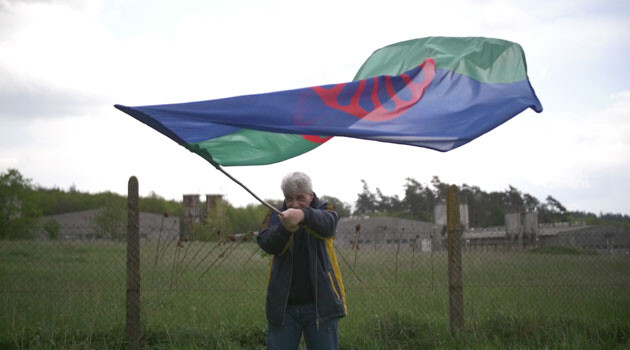Jozef Miker waves the Roma flag in front of the pig farm that occupies the site of the former concentration camp for Romani people at Lety u Písku. (PHOTO:  © RomaTrial)