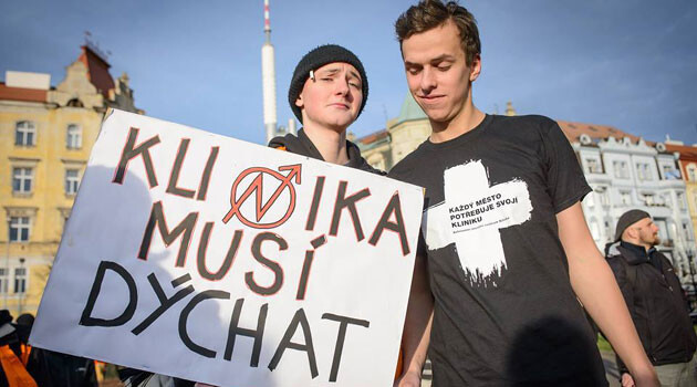 Two members of the Autonomous Social Center Klinika in Prague holding a sign that says
