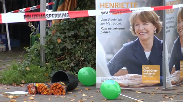 Candidate for Mayor of Cologne Henriette Reker was stabbed with a knife by a man at a marketplace on 17 October 2015. The apparently anti-immigrant, political, xenophobic motivation for the crime was confirmed by detectives during a press conference. (PHOTO:  Screenshot from a Reuters video)