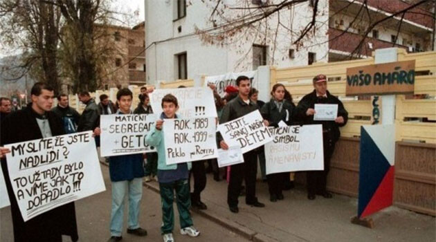 The concrete barrier on Matiční Street in Ústí nad Labem, Czech Republic being protested in 1999 by Romani people whose signs read