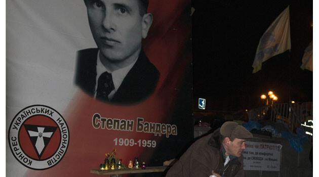A man sitting beneath a portrait of Stepan Bandera. (PHOTO:  Vít Hassan)