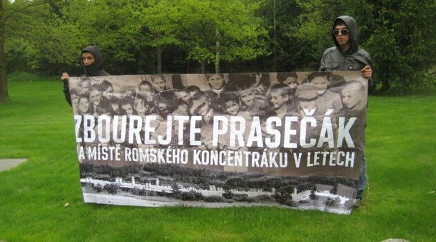 Activists during the commemorative ceremony at Lety by Písek holding a sign that reads