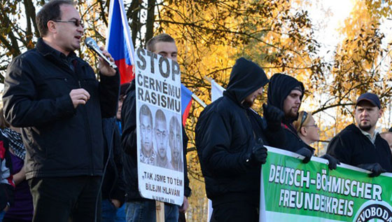 "Chair of the DSSS, Tomáš Vandas (holding microphone) speaking in Rotava. Far right, wearing the baseball cap, is German neo-Nazi Robin Siener (NPD and Freies Netz Süd). Standing behind the banner, which reads ""Czech-German Friendship"" is Katrin Köhler, a Saxon neo-Nazi with the NPD. Photo:  Antifa.cz."